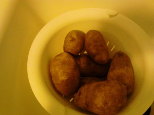 Potatoes in a colander in a sink, a good way to rinse potatoes.